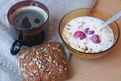 Muesli with fresh raspberries and milk, bread and coffee, typica Stock Image
