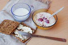 Muesli with fresh raspberries and milk, rye bread  with butter,. Typical Scandinavian breakfast Royalty Free Stock Photo