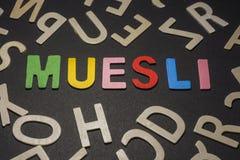 Muesli geschrieben mit bunten hölzernen Buchstaben auf ein schwarzes backgroun Lizenzfreies Stockfoto