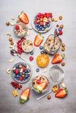 Muesli or granola in jars, fresh berries, seeds and  nuts  , top view. Stock Image