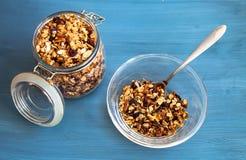 Muesli hecho en casa en una placa en un fondo azul, un desayuno sano del muesli de la harina de avena, nueces, semillas y frutas  fotografía de archivo
