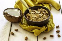 Muesli met kokosnoot en banaan op een witte houten achtergrond stock afbeelding