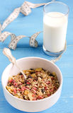 Muesli with milk and a measuring tape. On the blue background stock images