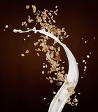 Muesli with milk. Splash against brown background stock photography