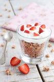 Muesli mit Creme und Erdbeere auf Holztisch Lizenzfreie Stockfotos