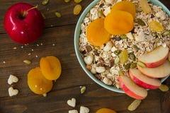 Muesli mit getrockneten Aprikosen und Äpfeln auf einer Tabelle in einer Platte Lizenzfreie Stockfotos