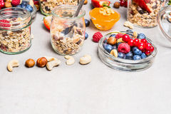 Muesli mix with nuts and berries in glass jars on light background, close up Stock Image