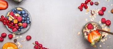 Muesli, Nüsse und Beeren Frühstücksvorbereitung Granola mit frischen Beeren im Glas auf Steinhintergrund, Draufsicht, Fahne Stockfoto