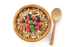 Muesli with nuts and fresh berries in a wooden bowl. Royalty Free Stock Images