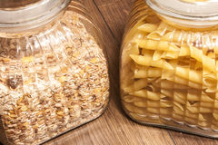 Muesli and penne pasta in glas pots. On wooden background Stock Photo