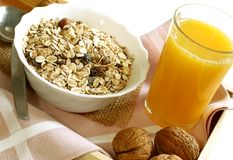 Muesli with raisins in bowl, glass of orange juice Royalty Free Stock Photos