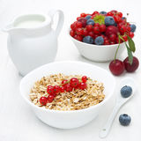 Muesli with red currant, bowl of fresh berries and jug of milk Stock Image