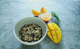 Muesli, sesame, mango and orange, and rosemary. / grey table Stock Photos