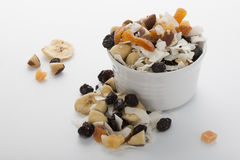 Muesli in small bowl. Some musli on the white background and some piled in white porringer Royalty Free Stock Photos