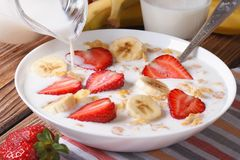 Muesli with strawberries, banana and milk is poured from a jug Royalty Free Stock Image