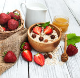 Muesli with strawberries. Milk and honey on a old wooden table Stock Photos