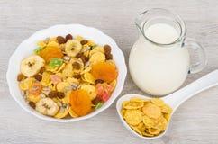 Muesli in witte kom, kruikmelk en lepelcornflakes Stock Foto