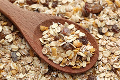 Muesli in a wooden spoon. On muesli background. Close-up Stock Images