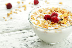 Muesli with yogurt and raspberries in a bowl on a white wooden background. Muesli with yogurt and raspberries in a bowl on a white wooden background Royalty Free Stock Images