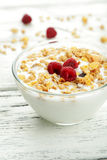 Muesli with yogurt and raspberries in a bowl on white wooden background Stock Images