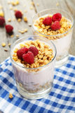 Muesli with yogurt and raspberries in a glass on a brown wooden background. Royalty Free Stock Images