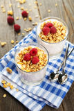 Muesli with yogurt and raspberries in a glass on a brown wooden background. Royalty Free Stock Photography
