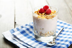 Muesli with yogurt and raspberries in a glass on a brown wooden background Royalty Free Stock Photos
