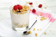 Muesli with yogurt and raspberries in a glass on a white wooden background. Stock Photography