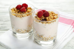 Muesli with yogurt and raspberries in a glass on a white wooden background Royalty Free Stock Photo