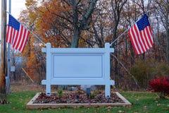 Muestra al aire libre en blanco con las banderas americanas Imagen de archivo