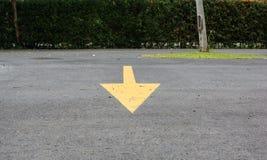 Muestra amarilla de la flecha de al revés al frente en estacionamiento Fotografía de archivo