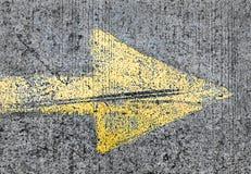 Muestra amarilla de la flecha en la calle Fotografía de archivo