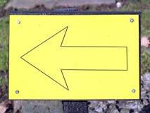 Muestra amarilla de la flecha que señala esta manera dejada Fotografía de archivo libre de regalías