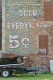 Muestra antigua pintada en la pared de ladrillo exterior imágenes de archivo libres de regalías