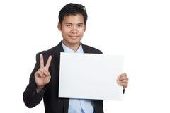 Muestra asiática de la victoria de la demostración del hombre de negocios con la muestra en blanco Fotos de archivo libres de regalías