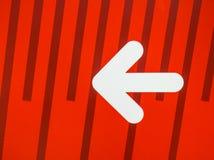 Muestra blanca de la flecha en fondo rojo Imágenes de archivo libres de regalías
