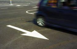 Muestra blanca de la flecha en la carretera de asfalto Imagenes de archivo