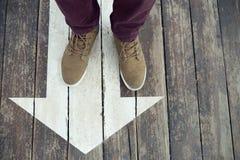 Muestra blanca de la flecha en piso de madera Las piernas del hombre que se colocan en la muestra de la flecha pintada en el piso foto de archivo libre de regalías