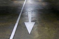 Muestra blanca del símbolo de la flecha en el estacionamiento de la calzada del piso del cemento Fotografía de archivo