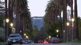 Muestra de Hollywood abajo de una calle alineada palmera en la última hora de la tarde
