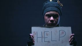 Muestra de la ayuda en el cartel en manos de la persona sin hogar, abuso de alcohol, falta de vivienda almacen de metraje de vídeo