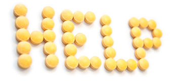 Muestra de la ayuda hecha fuera de píldoras anaranjadas Fotografía de archivo libre de regalías