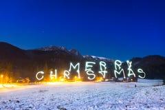 Muestra de la Feliz Navidad debajo de las montañas de Tatra en la noche Imagen de archivo