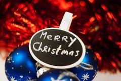 Muestra de la Feliz Navidad en fondo chispeante azul-rojo Fotos de archivo
