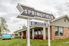Muestra de la flecha del camino de Springfield con el fondo del café Imagen de archivo