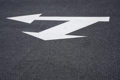 Muestra de la flecha direccional en el asfalto Imagen de archivo libre de regalías