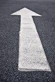 Muestra de la flecha direccional en el asfalto Imagenes de archivo