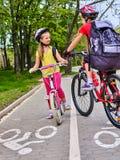 Muestra de la trayectoria de la bicicleta con los niños Muchachas que llevan el casco con la mochila Imagenes de archivo