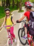 Muestra de la trayectoria de la bicicleta con los niños Muchachas que llevan el casco con la mochila Foto de archivo