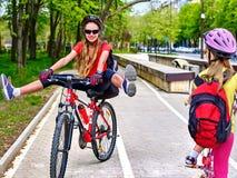 Muestra de la trayectoria de la bicicleta con los niños Muchachas que llevan el casco con la mochila Imagen de archivo